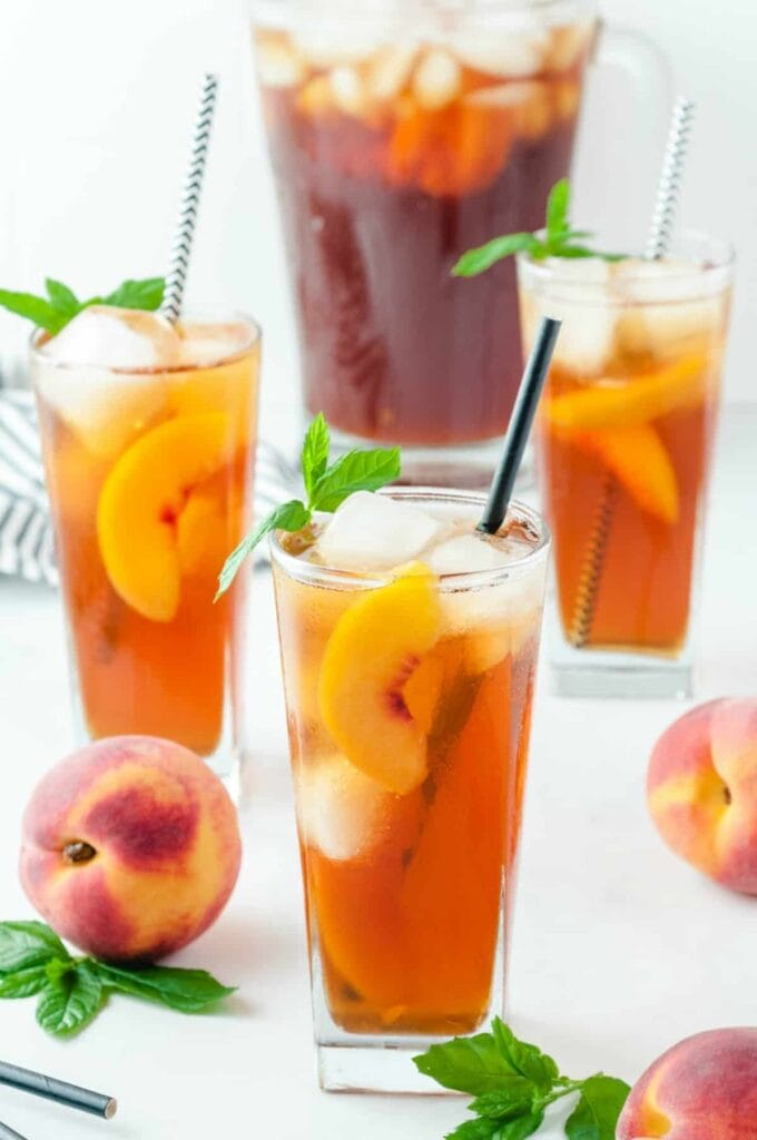 3 glasses of peach iced tea with a pitcher of iced team behind it and peaches surrounding the glasses