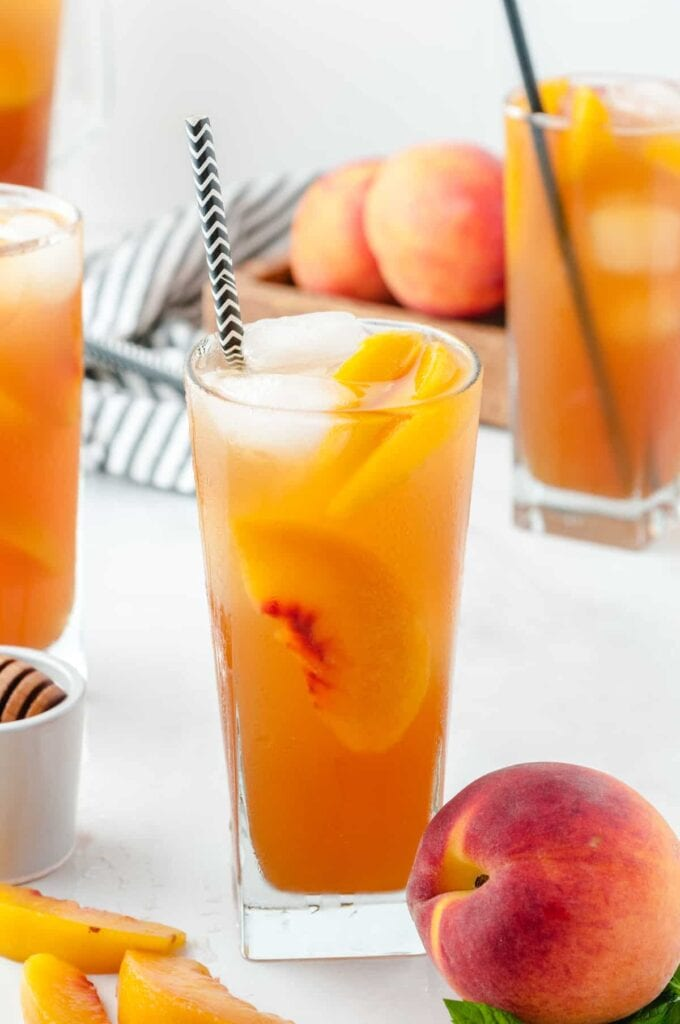 glass of peach ice tea with a peach next to it