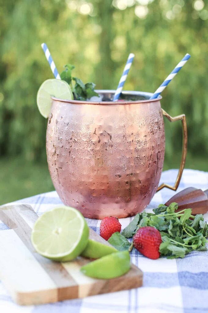 Moscow mule in a copper mug with striped straws and limes and strawberries on the table with mint leaves