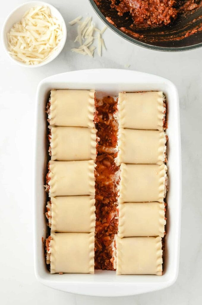 rolled up lasagna noodles in a casserole dish