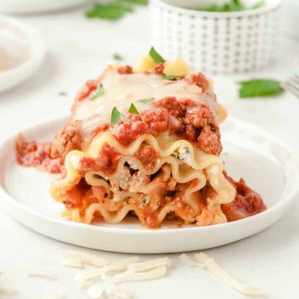 Lasagna Roll-Ups on white plate with cheese on top