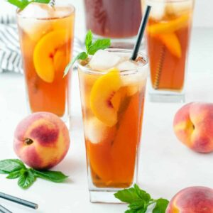 peach iced tea with a piece of peach floating in the glass and a peach next to it on the table