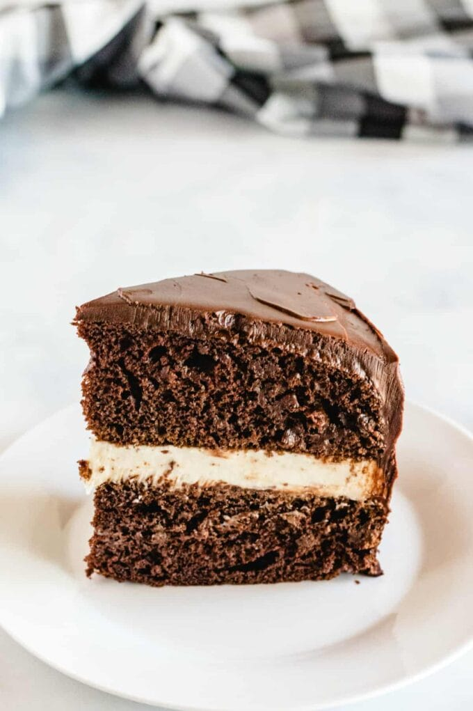 slice of chocolate cake with cream filling and chocolate ganache