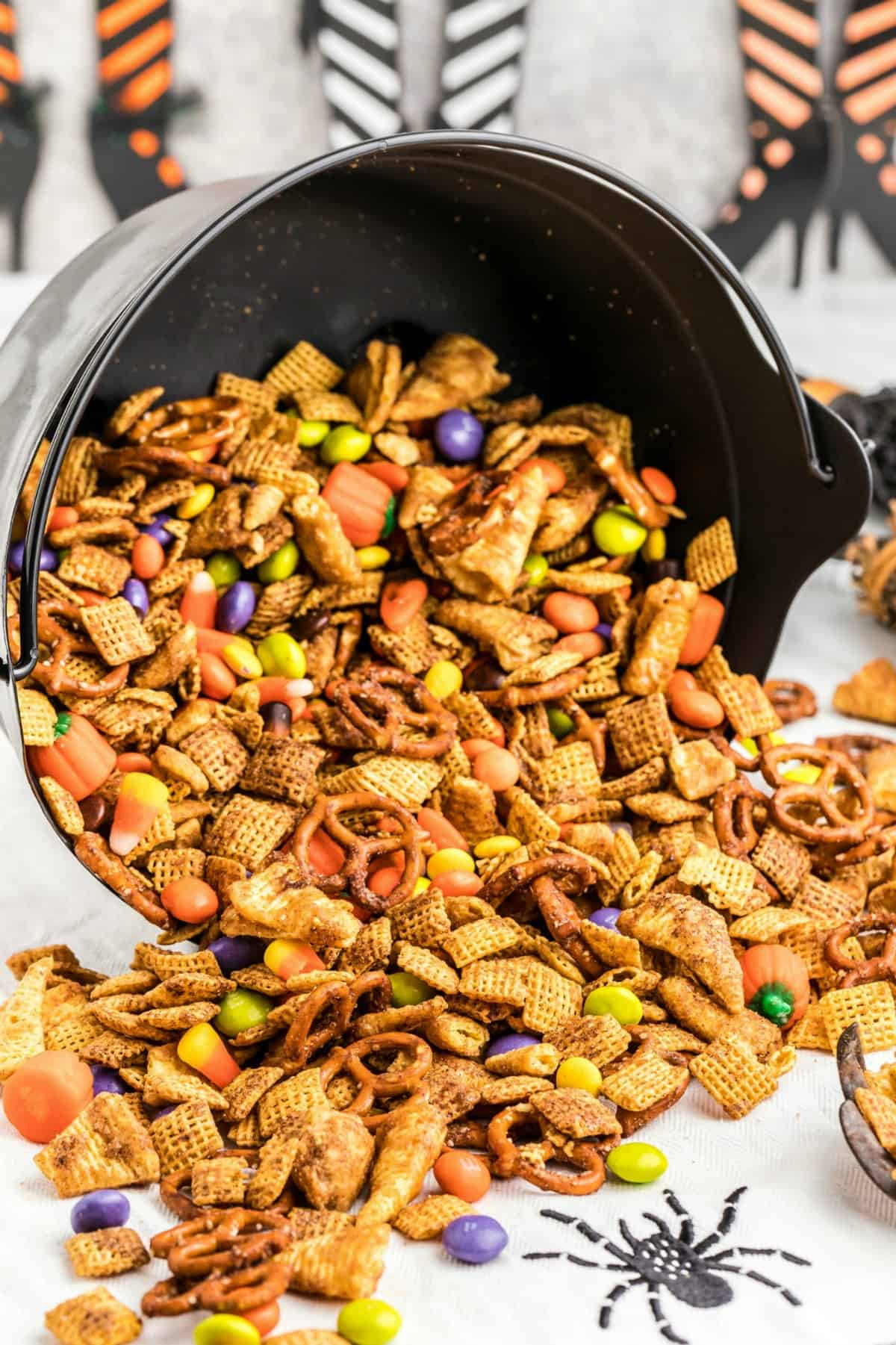Halloween Chex Mix spilling out of a black cauldron