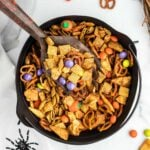 Halloween Chex Mix in a black bowl with a spider on the table cloth