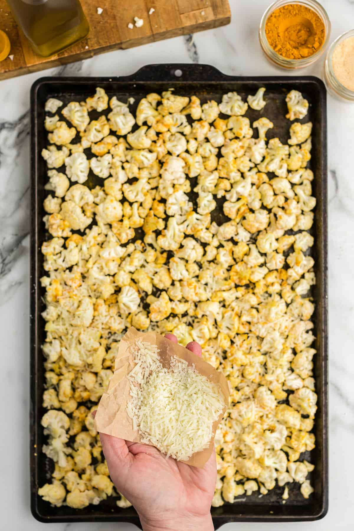 cauliflower on a baking pan with parmesan cheese