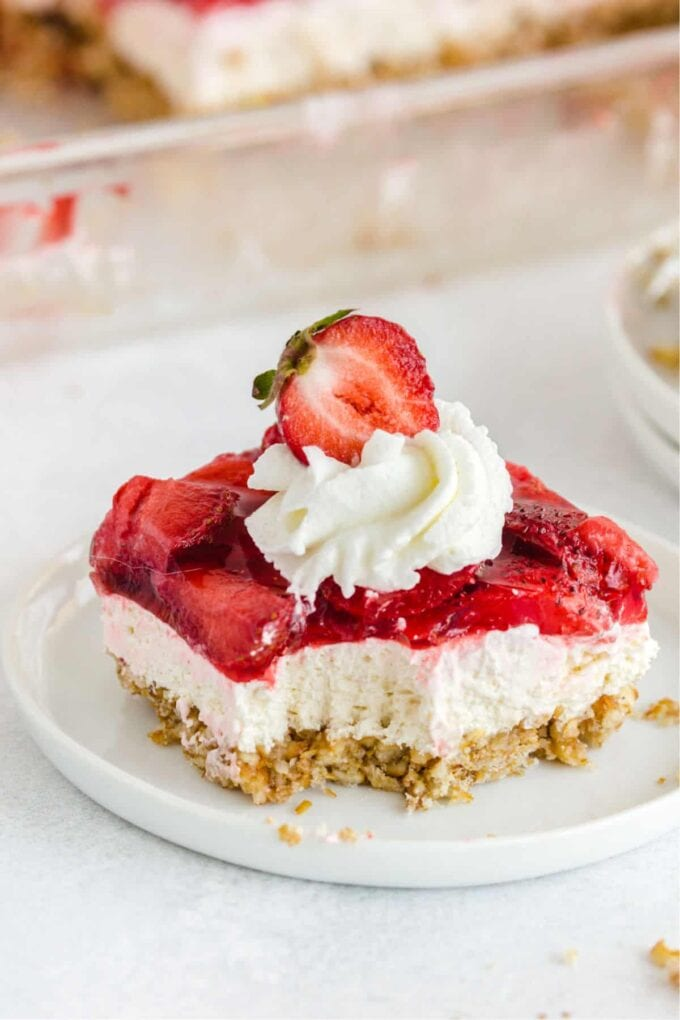 Strawberry Pretzel Salad on a white plate with cool whip and a strawberry on top
