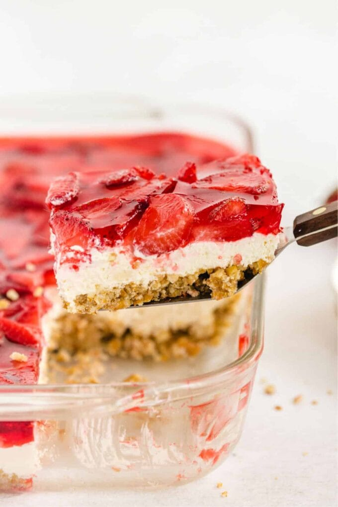 Slice of Strawberry Pretzel Salad on a spatula with a baking dish in the background