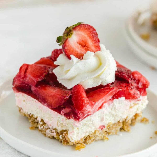 Strawberry Pretzel Salad on a white dish with whipped cream and a sliced strawberry on top