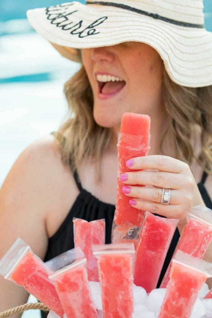 woman holding popsicle in hand with a hat on