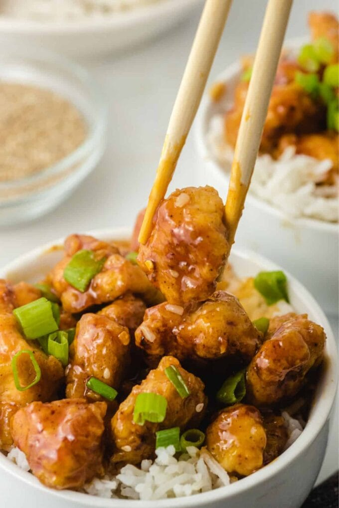 firecracker chicken in a white bowl on rice with chopsticks