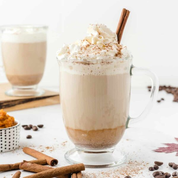a homemade latte with pumpkin spice sprinkled on top and a cinnamon stick coming out