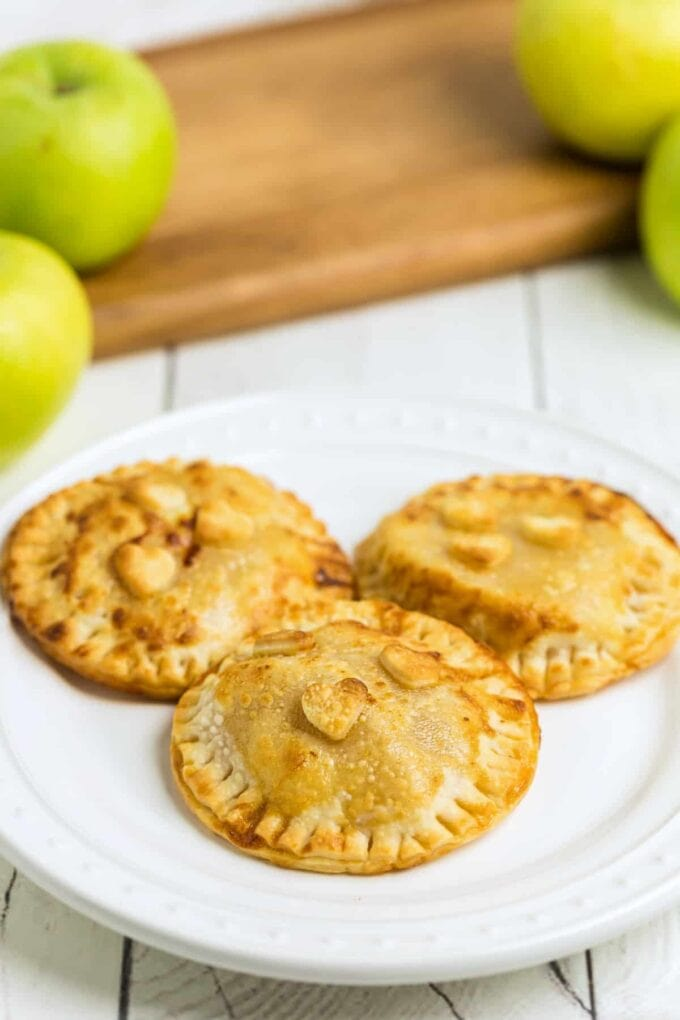 Caramel Apple Hand Pies on a white plate with apples in the background