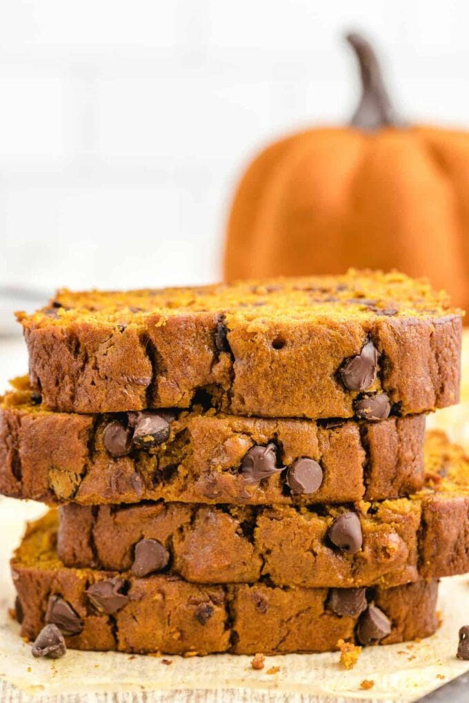 stacked sliced of chocolate chip pumpkin bread with a pumpkin in the background