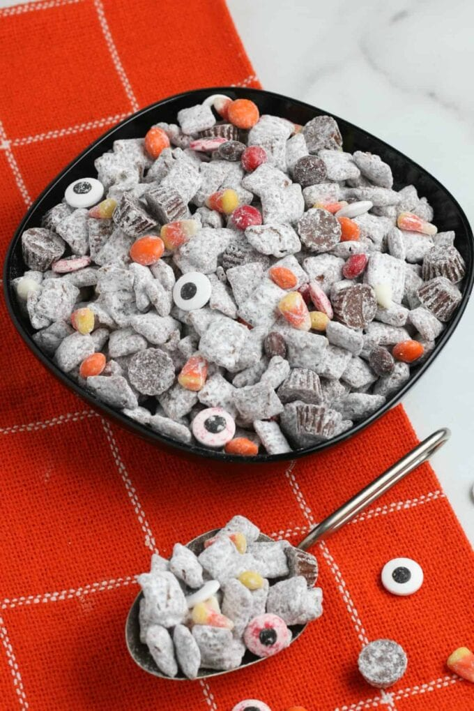 puppy chow with Halloween candy in a black bowl