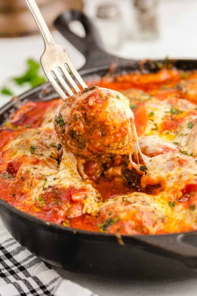meatballs in red sauce with cheese in a cast iron skillet
