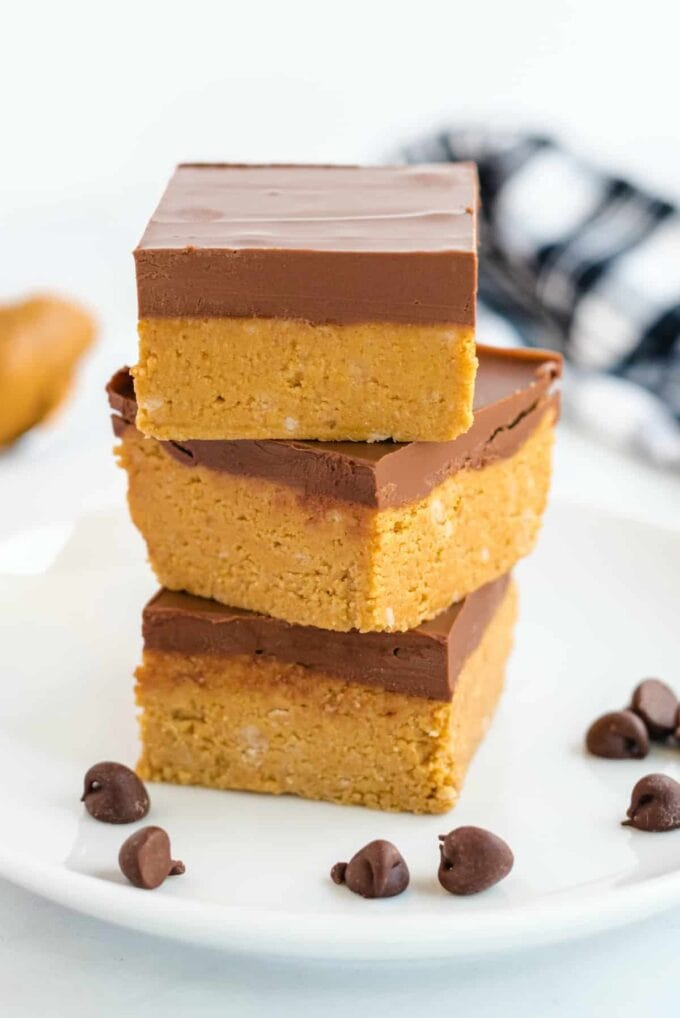 chocolate peanut butter squares stacked on a white plate