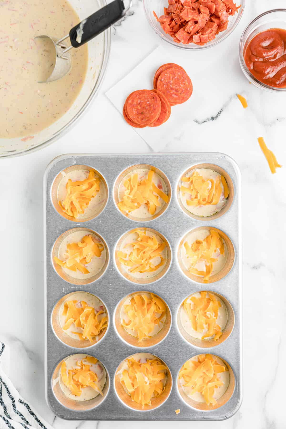 cheese on top of batter in a muffin tin