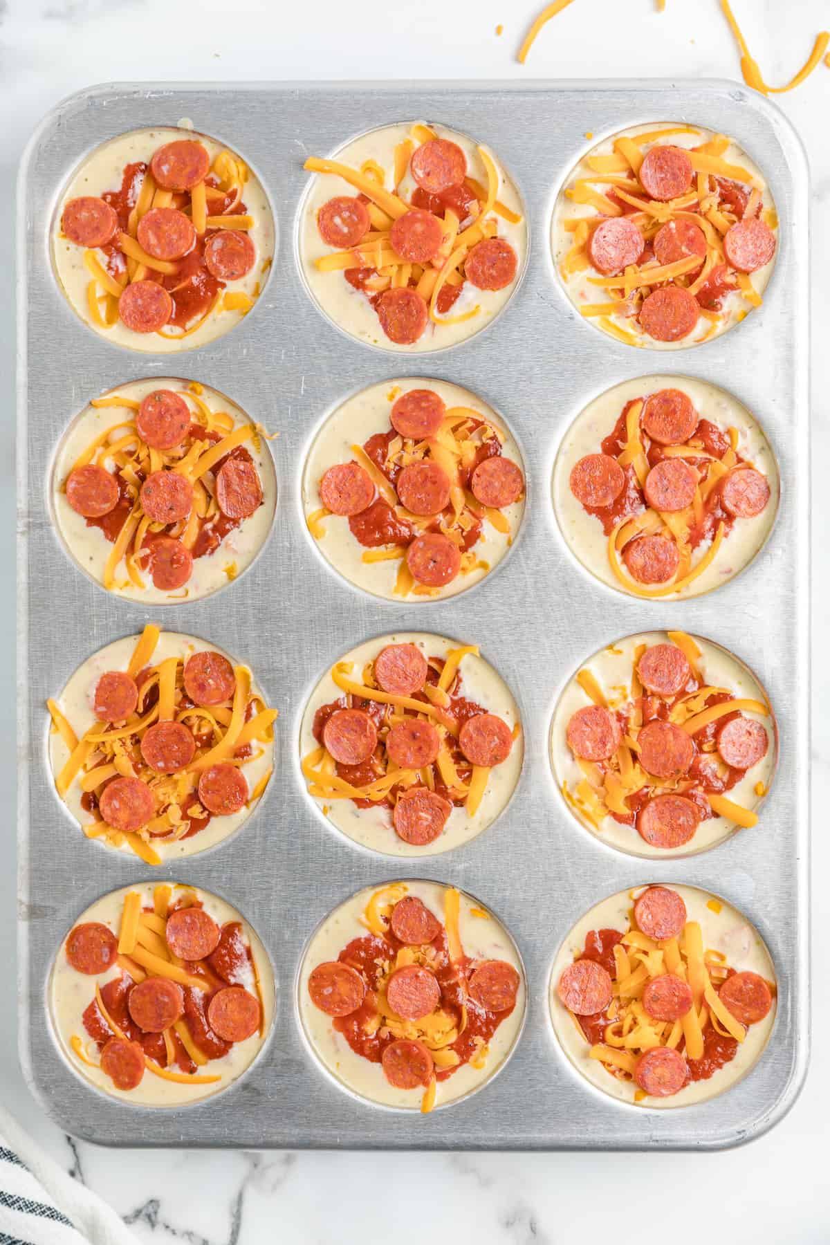 pepperoni on top of the batter in the muffin tin