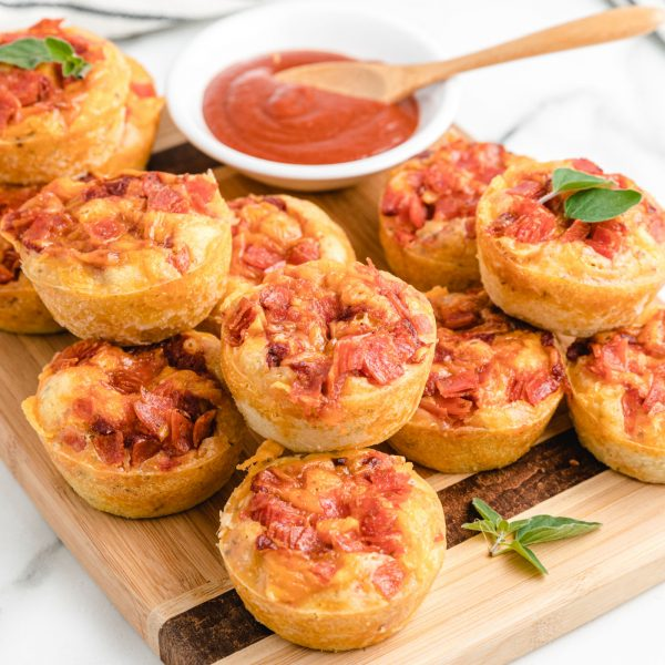 Pizza muffins stacked on a cutting board