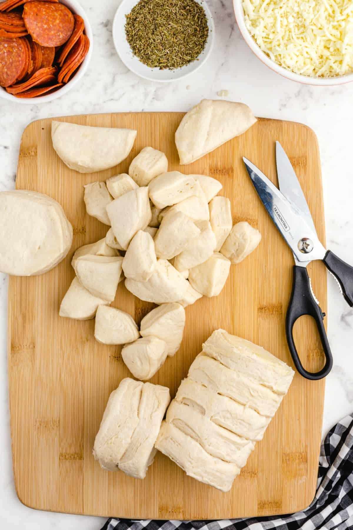 cutting biscuits in quarters on a cutting board