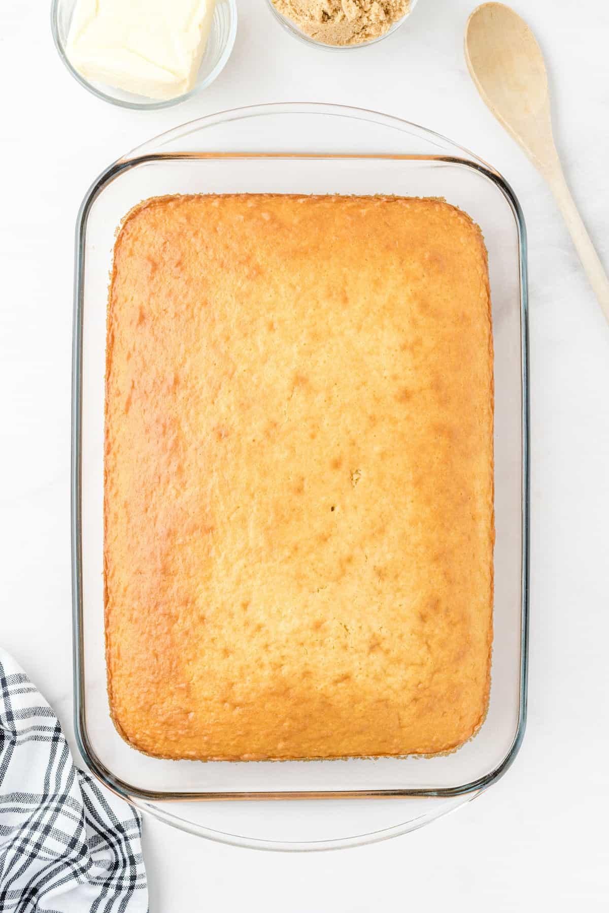 cinnamon roll poke cake cooling in pan