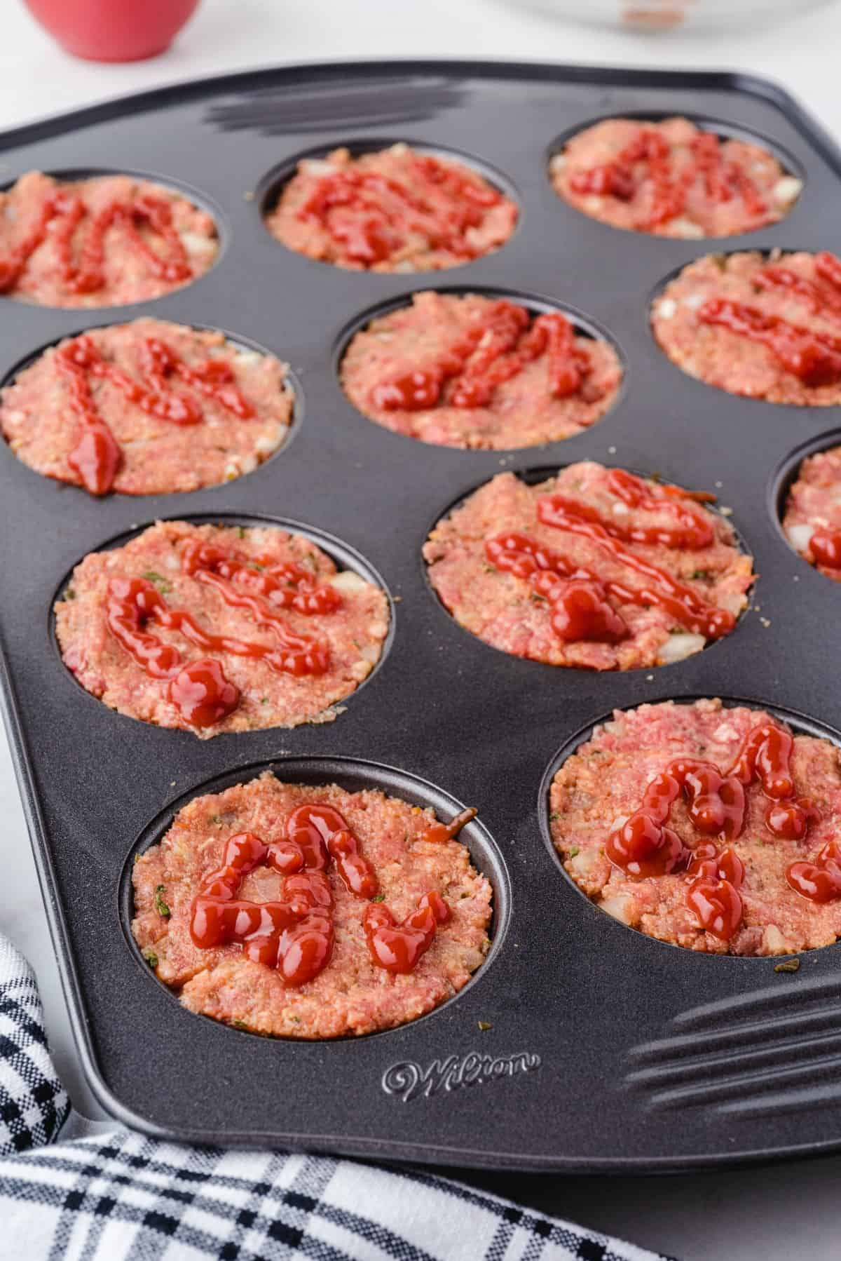 ketchup on meatloaf in muffin pan