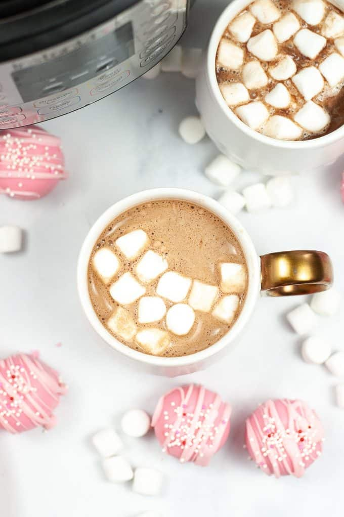 mug of hot chocolate with marshmallows in it and pink hot chocolate bombs surrounding it