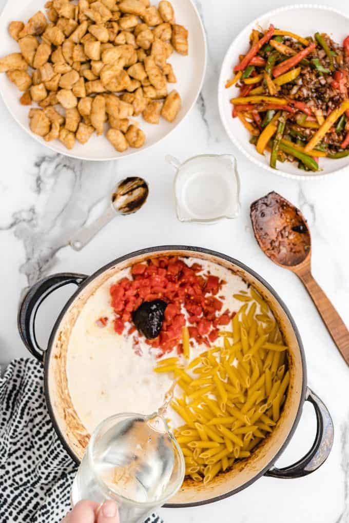 Adding water, better than bouillon chicken base, heavy cream, rotel tomatoes, garlic powder, onion powder, and penne pasta