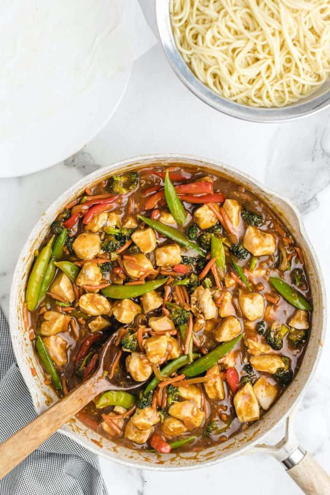 chicken lo mein in a pan with wooden spoon