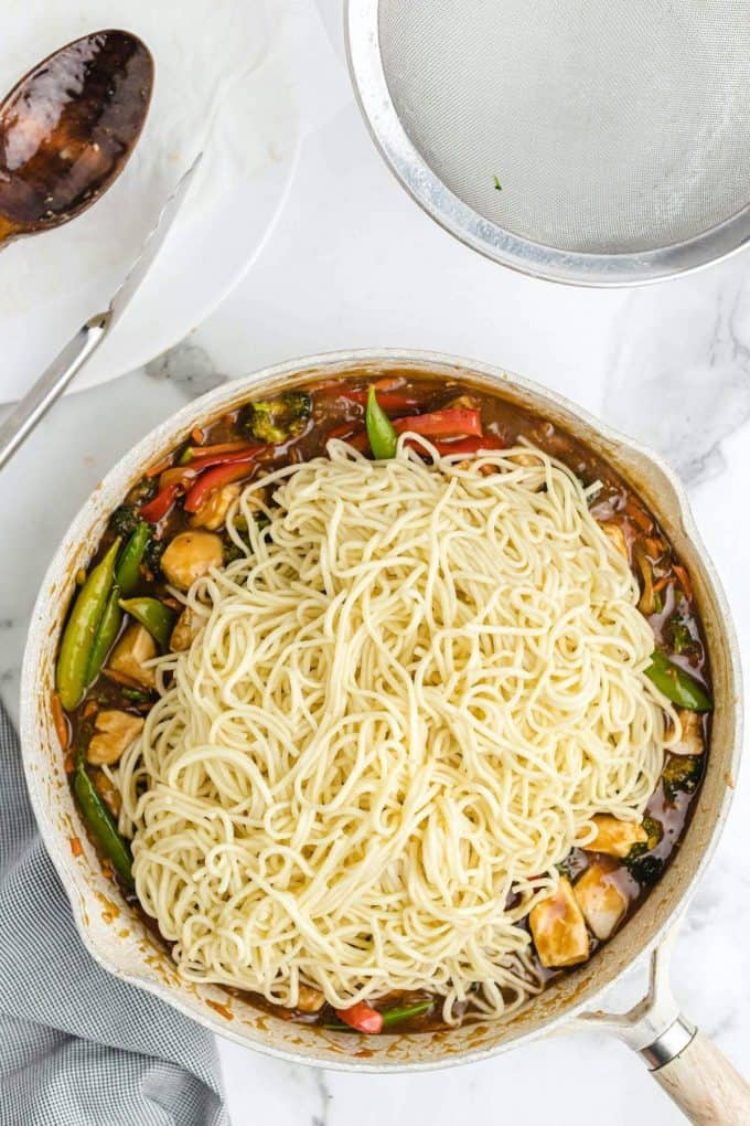 lo mein noodles added to a pan of veggies with brown sauce