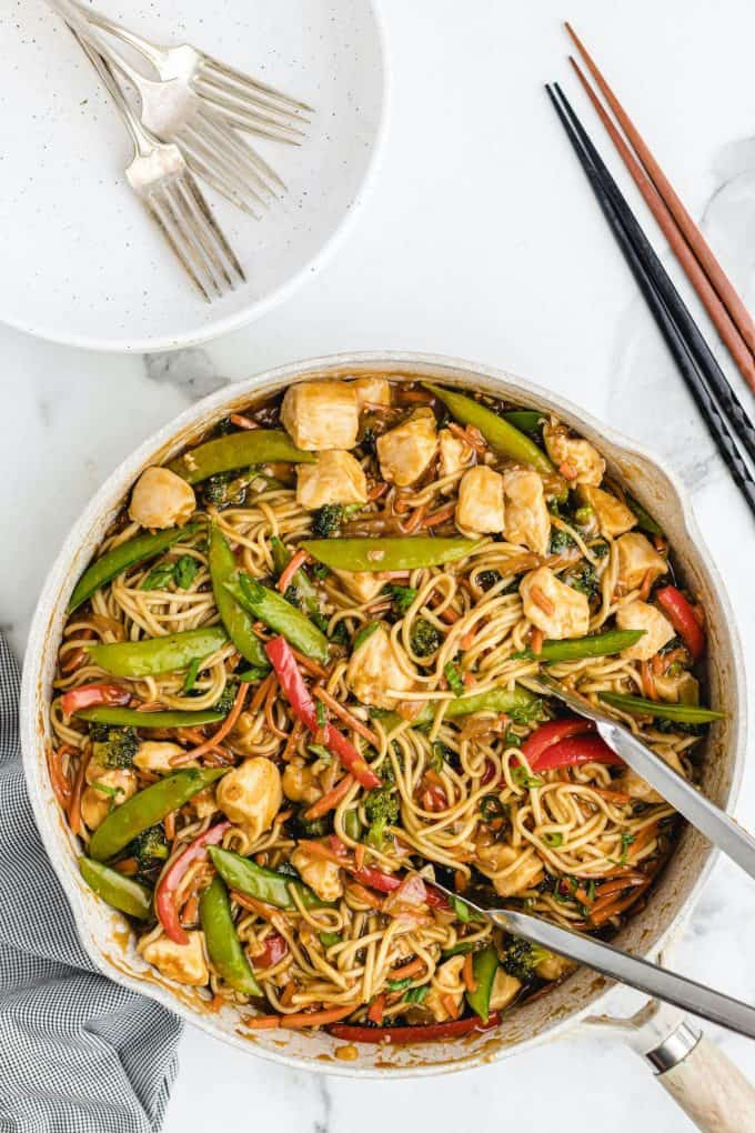 Chicken Lo Mein in a pan with tongs