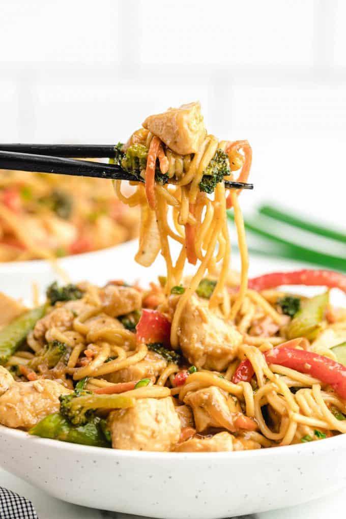 lo mein with chicken in chopsticks