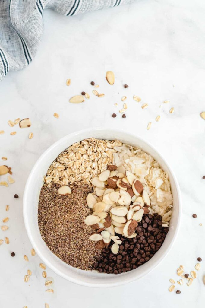 old fashioned oats, shredded coconut, ground flaxseed, semi-sweet chocolate chips, and sliced almonds in a bowl