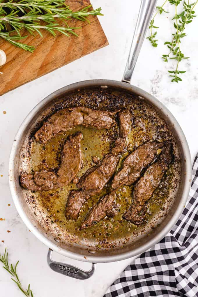 several strips of brown meat in a skillet