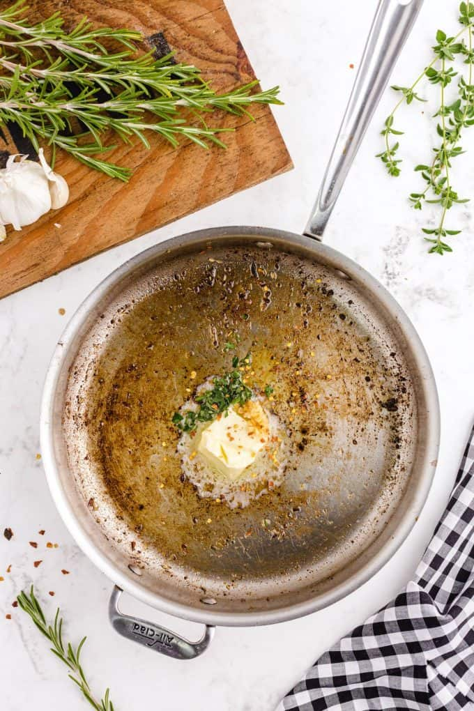 butter, cloves of minced garlic, red pepper flakes, the fresh rosemary and oregano in a skillet