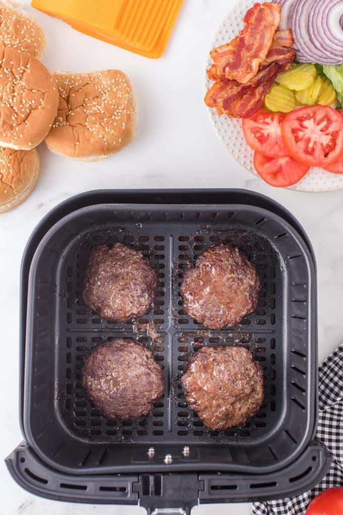 four well cooked patties in air fryer basket