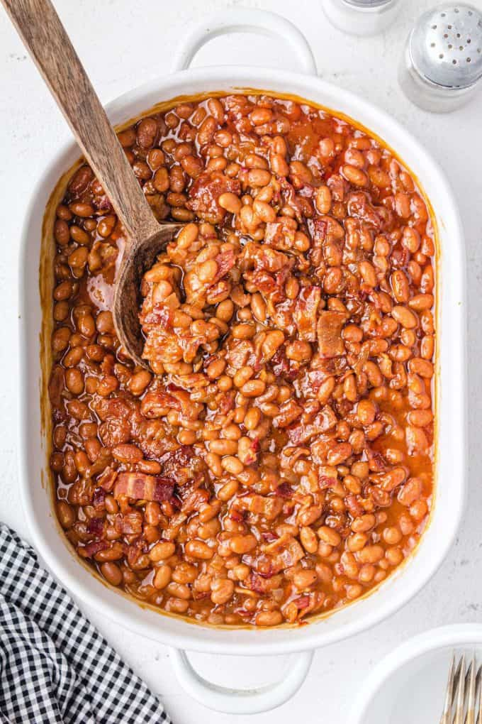 baked beans being scooped out using wooden spoon