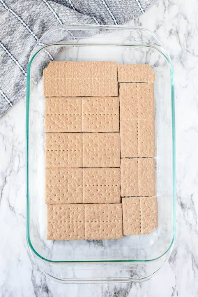 putting the first layer of graham crackers in baking dish