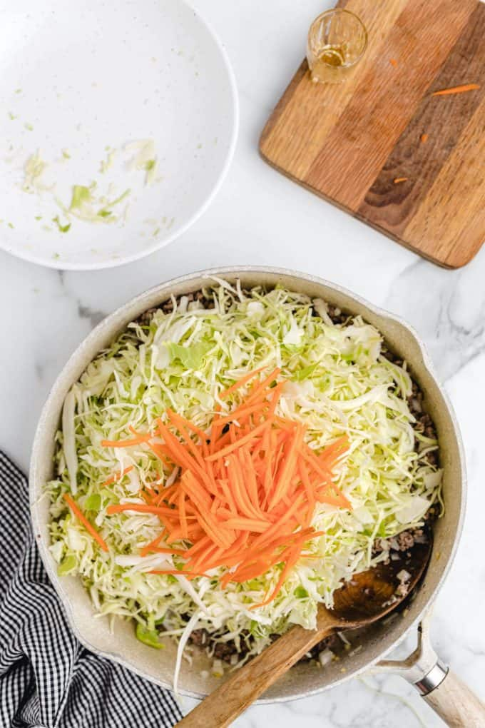 Add sesame oil, carrots, and cabbage into the pan