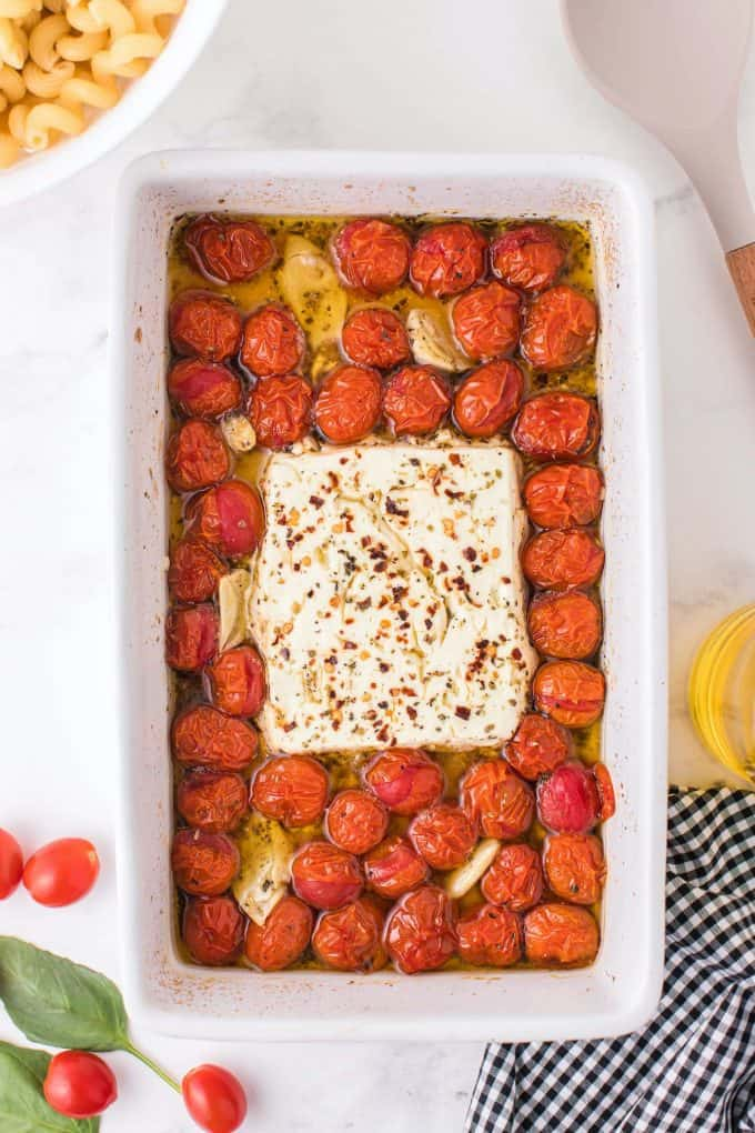 baked tomatoes, feta cheese and garlic cloves in a baking dish