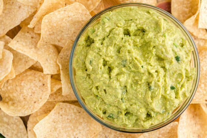 guacamole in a bowl in the middle of chips