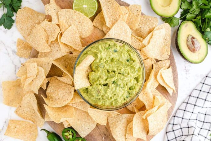 guacamole in a bowl with chips dipped in