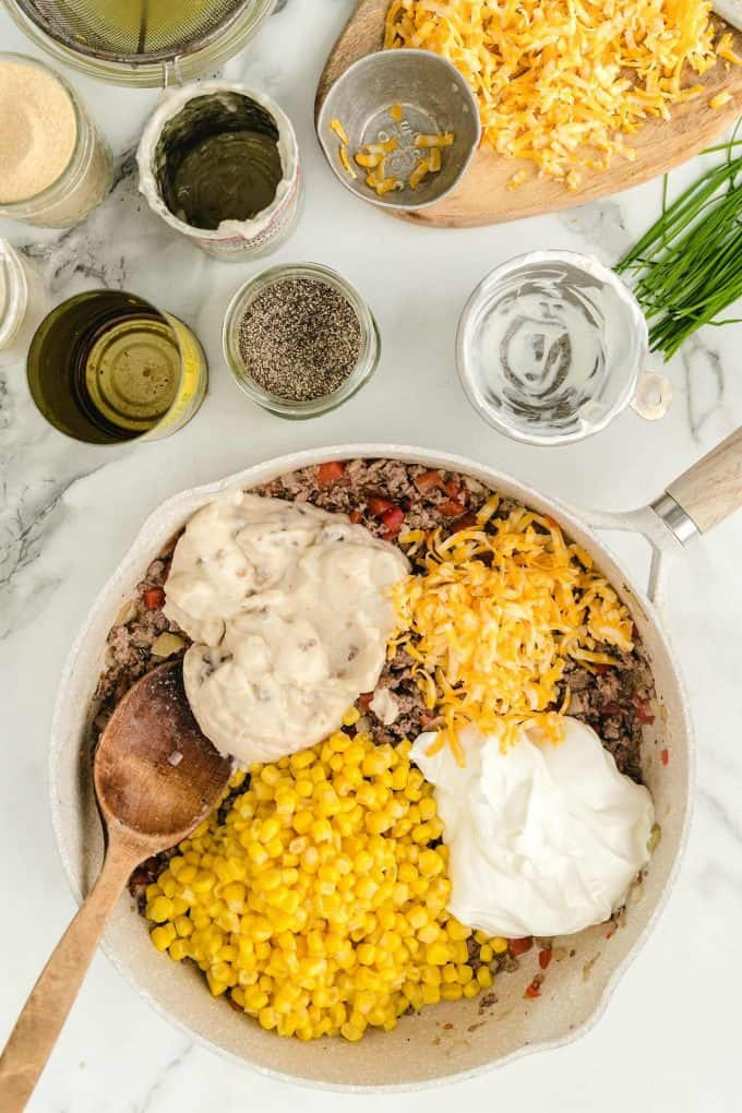 add sour cream, cream of mushroom soup, drained corn, ½ cup of cheese into the skillet