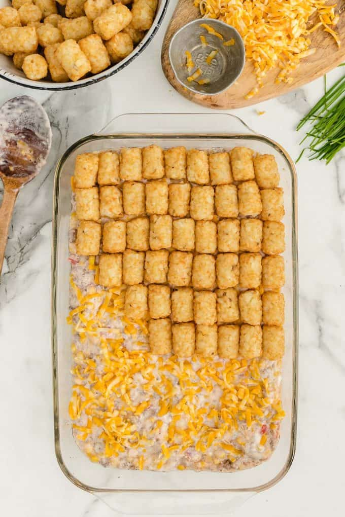 sprinkle cheese on top of the casserole and add the tater tots on top of the cheese