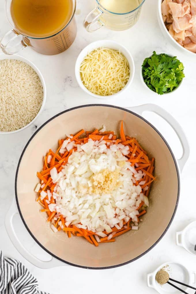 adding grated carrots, diced onion, minced garlic into the pot