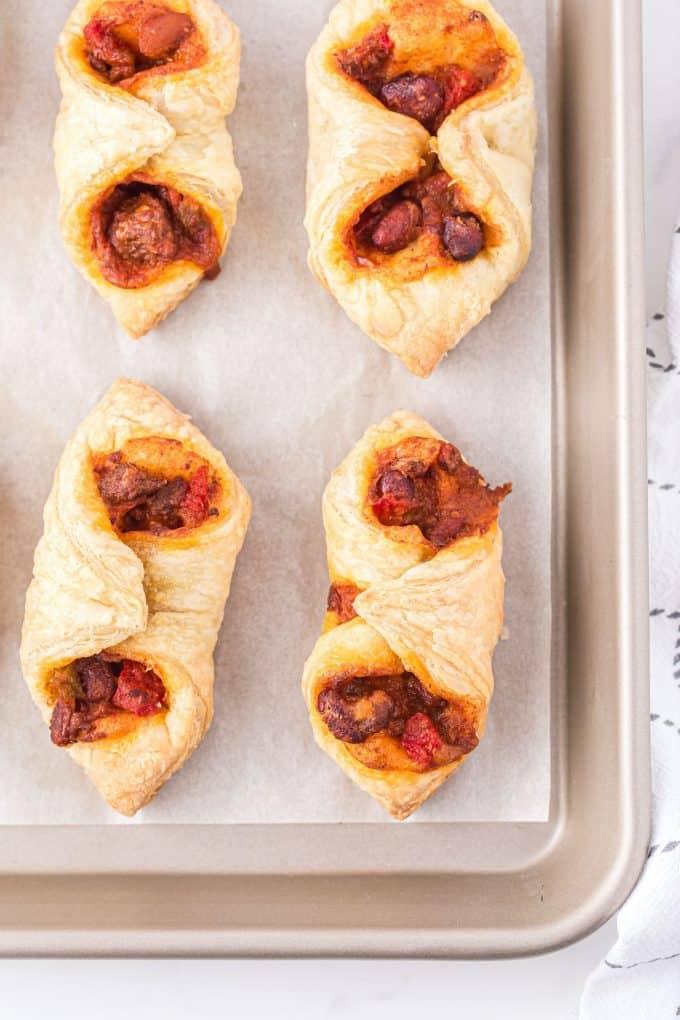 4 puffy tacos in a baking sheet