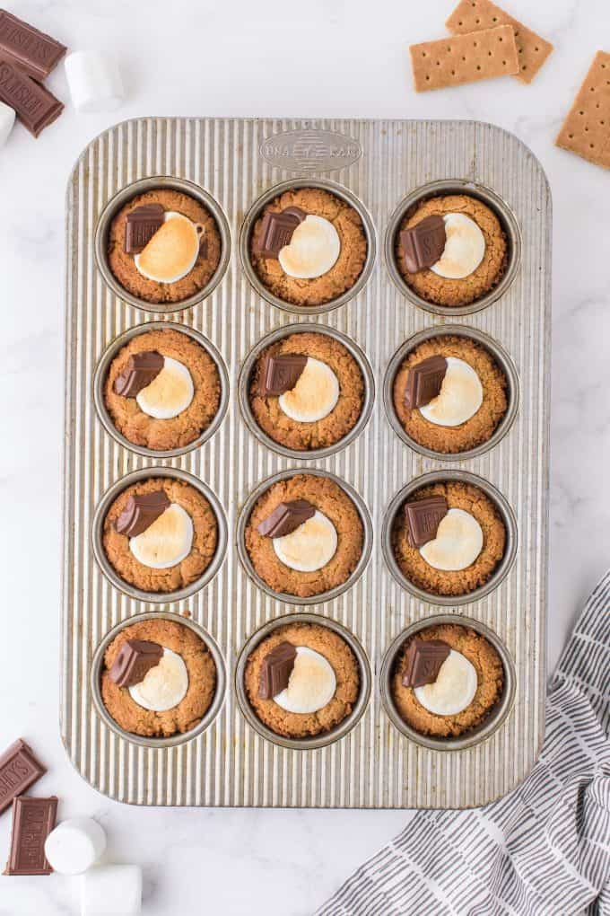 smores cookie cups ready in a muffin tin