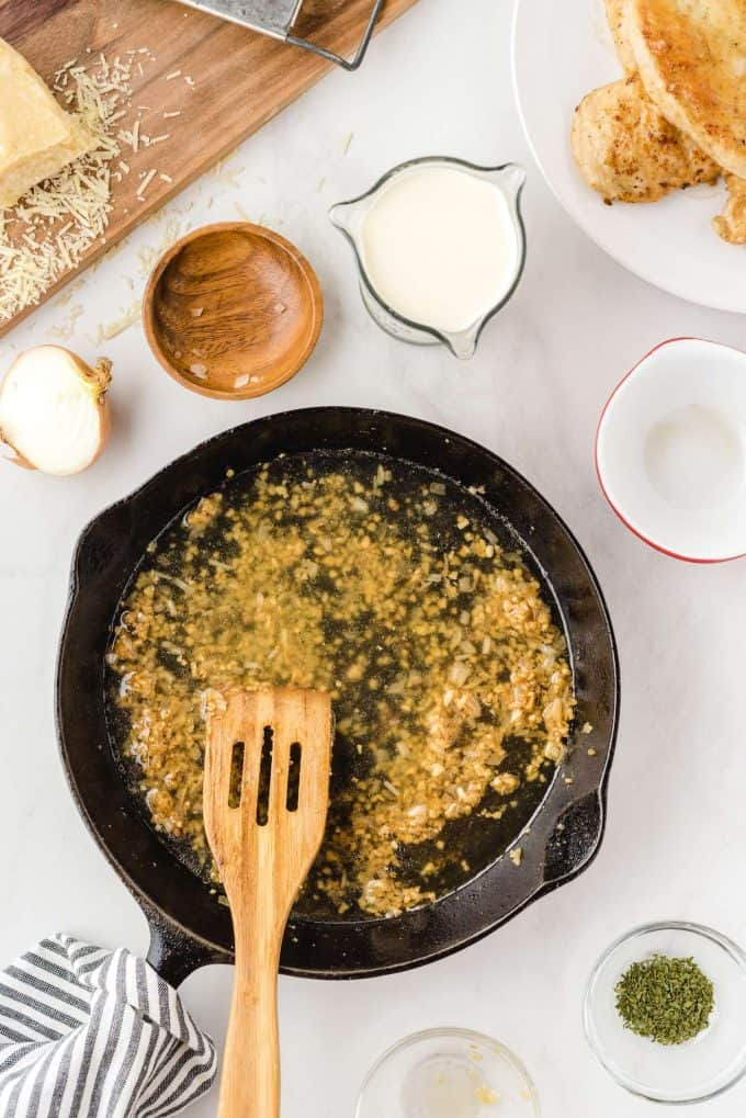 adding minced garlic to the pan