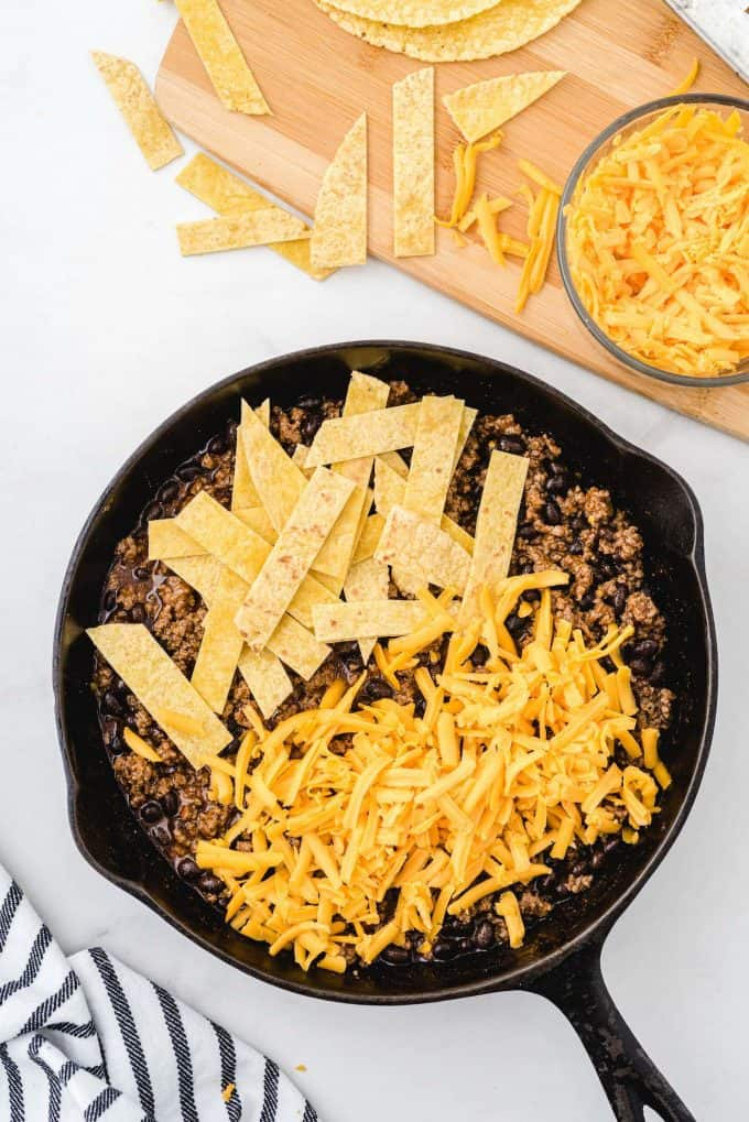 stirring strips and cheese together with the ground beef